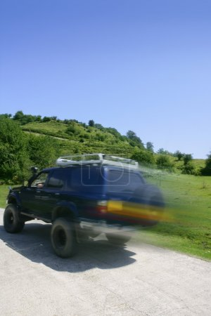 Blurred motion speedy 4x4 truck in meadow
