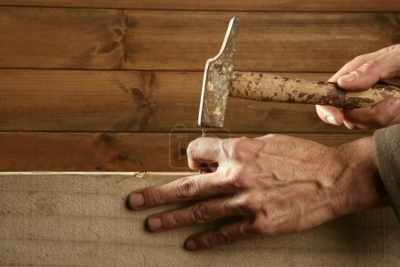 Carpenter hands with hammer wood and nail