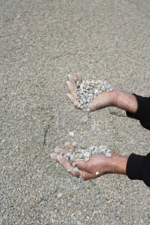 Gravel rolling stones falling man hands in quarry