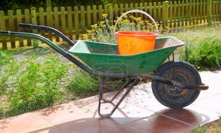 Gardener green wheel barrow with orange pail