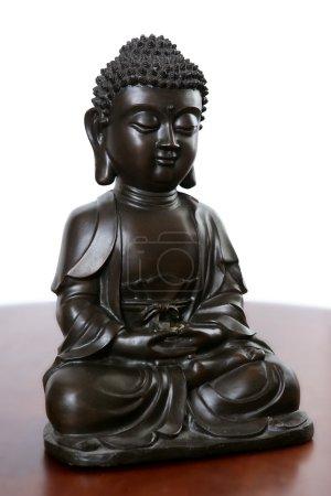 Photo pour Bouddha petite sculpture noire sur table en bois rouge - image libre de droit