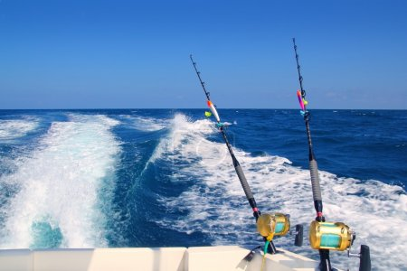 Photo pour Pêche à la traîne canne à pêche bateau et golden eau salée moulinets sillage mer océan bleu profond - image libre de droit