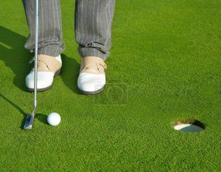 Photo pour Homme de cours de trou vert Golf mettant le ballon à l'intérieur de putt court - image libre de droit