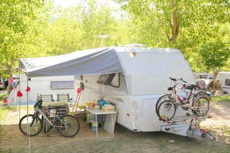 Photo pour Camping camping caravane arbres parc avec vélos - image libre de droit