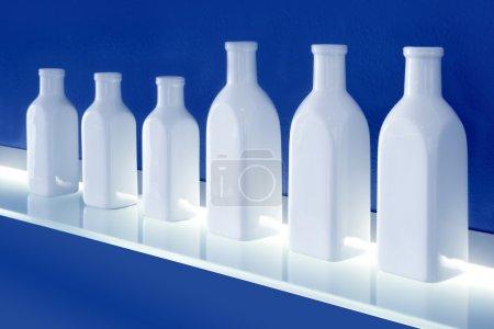 White bottles row on blue background shelf