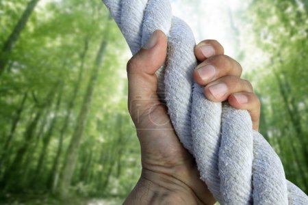 Man hand grab grip climbing green forest rope