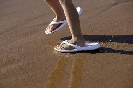 Photo pour Chaussure adulte pour enfants pieds sur la plage sable extérieur - image libre de droit