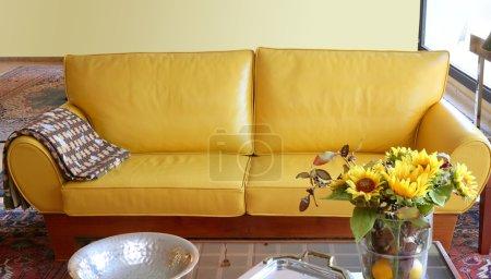Yellow leather sofa interior sunflower bouquet
