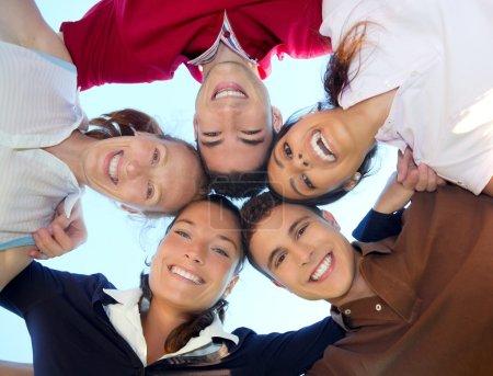 Photo pour Amis heureux groupe en cercle têtes souriant ensemble de dessous vue - image libre de droit