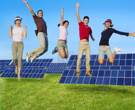 Foto de Saltar jóvenes feliz grupo de energía verde placas solares - Imagen libre de derechos