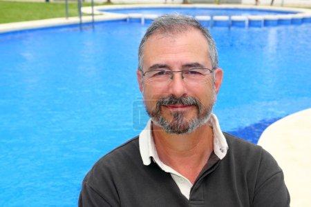 Photo pour Senior souriant vacances de homme en bleu piscine heureux à la retraite - image libre de droit
