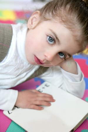 Photo for Beautiful preschooler little girl sutdent learning with homework book - Royalty Free Image