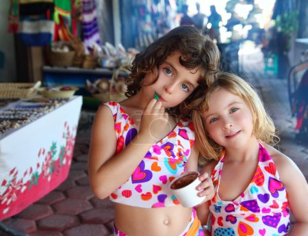 Sister little girls eating chocolate ice cream summer