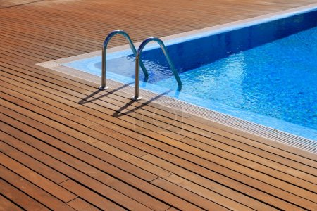 Photo for Blue swimming pool with teak wood flooring stripes summer vacation - Royalty Free Image