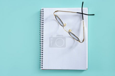 Doctor teacher glasses on blank spiral notebook