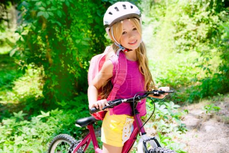 Children girl riding bicycle outdoor in forest smiling