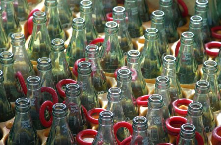Photo for Row of empty glass bottles with rings, ring toss bottle game at the carnival - Royalty Free Image