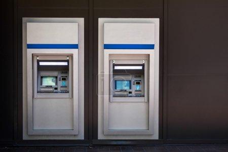 Photo pour Deux guichets automatiques côte à côte devant le bâtiment de la banque - image libre de droit