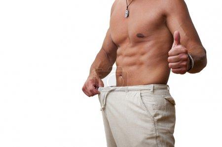 Photo pour Musclé et bronzé mâle dans un vieux pantalon après la perte de poids - image libre de droit