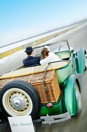 Photo pour La voiture de mariage rétro de voiture couple nouvellement marié - image libre de droit