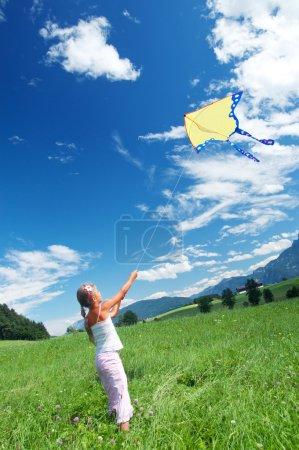 Photo pour Mignon enfant voler un cerf-volant dans le ciel bleu lumineux. affichage vertical - image libre de droit