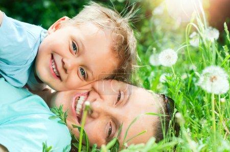 Photo pour Garçon mignon de 2 ans avec la mère allongée dans l'herbe à la journée d'été ensoleillée - image libre de droit