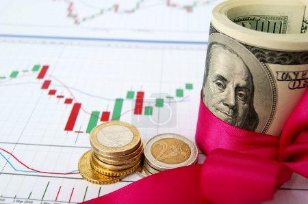 Photo pour Dollars US retroussé et serré avec une bande rose et pièces en euros sur l'arrière-plan du graphique change - image libre de droit