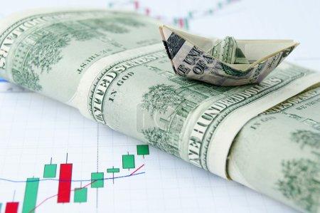 Photo pour Navire fait d'argent sur la vague de billets en dollars sur le fond du graphique de change - image libre de droit