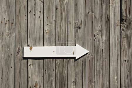 Old weathered wall or fence with wooden arrow sign