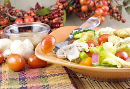 Photo for Colorful garden salad with mushrooms, tomatoes, and Italian dressing in orange bowl with fall colored table setting - Royalty Free Image