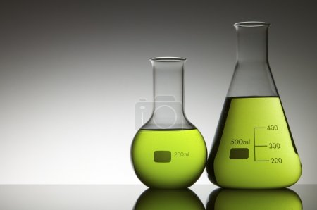 Photo for Two flasks with liquid bright green and white background - Royalty Free Image