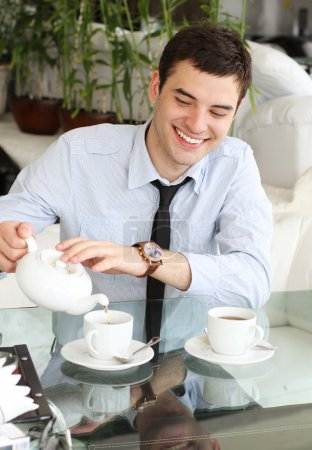 Smiling young men pours tea into a cup. Beautiful smile