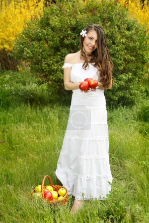 Beautiful girl with a basket in white dress holding a red apple
