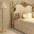 Luxurious bed with cushion and stand lamp in royal...