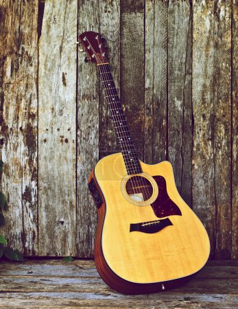 Photo for Image of a classical guitar on a grunge wood backdrop with copy space. - Royalty Free Image