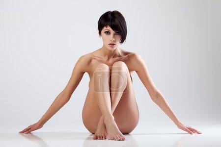 Foto de Joven hermosa mujer desnuda sentada en un piso - Imagen libre de derechos