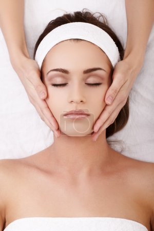 Photo for Beautiful young woman enjoying a facial massage - Royalty Free Image