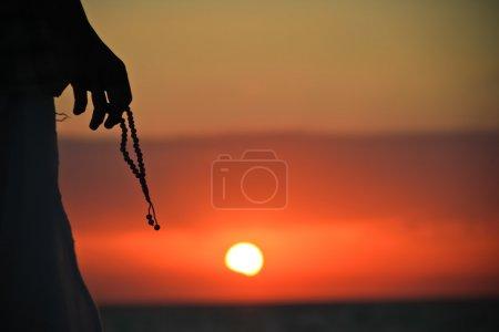 Photo pour Silhouette d'un homme avec un chapelet dans ses mains au coucher du soleil - image libre de droit
