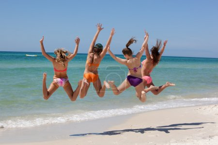 Photo for Four Teenage girls jumping high on a beach and having fun with arms wildly extended in the air, inflatable raft - Royalty Free Image