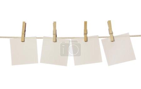Photo pour Quatre notes blanches suspendues sur la corde à linge isolée sur fond blanc - image libre de droit