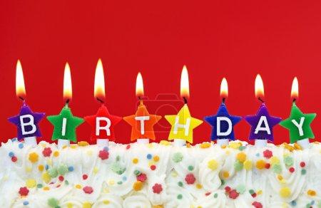 Foto de Velas de cumpleaños colorido sobre fondo rojo - Imagen libre de derechos