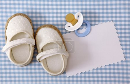 Baby white shoes on blue background