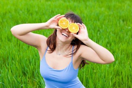 Photo pour Fille souriante regarde à travers l'orange sur une herbe - image libre de droit