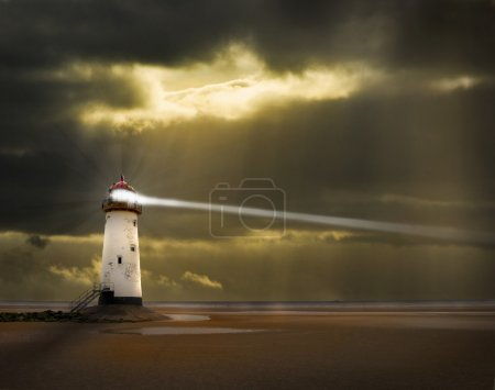 Lighthouse with beam and stormy sky