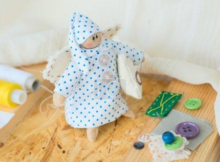 Photo pour Drôle de chiffon-poupée à la main avec fil et aiguilles - image libre de droit