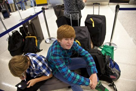Boys is sitting on thr baggage waiting for check in at the airport