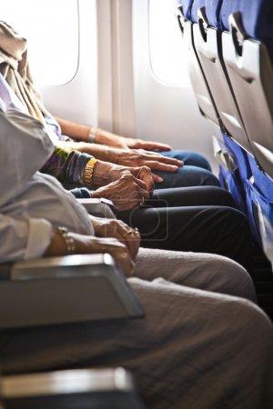 Photo pour Mains de passagers dans la cabine d'un aéronef - image libre de droit
