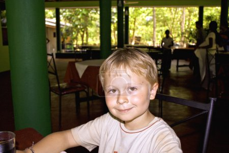 Boy sitting un the hotel area enjoys the vacation