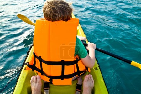 Boy paddling in a canoe at the ocean with safety west