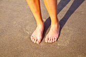 Feet of boy on the wet sand at the beach